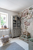 A grey dresser and a stack of suitcases in front of a floral wallpaper in a girl's room