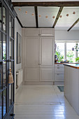 A view into a white kitchen with wooden floorboards