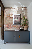 Entrance area with white painted wooden floor and brick wall, in front of it a gray painted lowboard