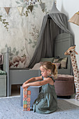 A girl playing in a children's room with a bed with a canopy in the background against floral wallpaper