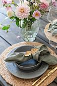 Gedeck und Blumenstrauß auf Terrassentisch