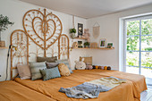 A bed with a rattan headboard in a cosy bedroom