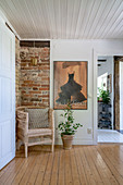 A rattan armchair in front of a brick wall on a landing with wooden floorboards