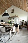 Pendelleuchten über Esstisch mit Freischwinger und Holzbank in offenem Wohnraum