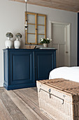 A rattan chest at the end of a bed and a blue sideboard in a bedroom
