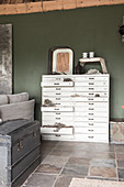 A shabby-chic style chest of drawers against a green wall