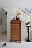 A gramophone on an antique chest of drawers and a stuffed pheasant on a stela in front of a flight of stairs