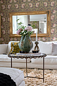 A vase of flowers on a coffee table, a white sofa and a gold-framed mirror on a wall with floral wallpaper