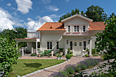 A white wooden house with a sunny garden