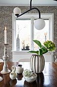 Porcelain decorations, a candle holder and a hydrangea in a vase on a dining table