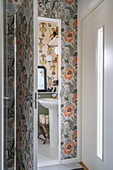 A view of a pedestal washbasin in a wallpapered guest toilet