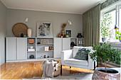 Helles Polstersessel im Wohnzimmer mit grauem Highboard vor grauer Wand