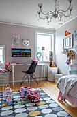 A desk with a chair in a girl's room with toys on the carpet in the foreground