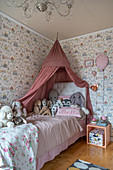 Cuddly toys on a bed with a canopy in a girl's room with wallpaper