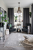 Schwarze Ledersessel und Beistelltisch vor Fenster