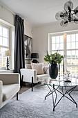 Runder Tisch mit Glasplatte und helle Polstermöbel im Wohnzimmer