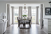 A dining area with upholstered chairs in front of French doors with curtains