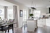 Dining area with upholstered chairs and kitchen island in the open living room
