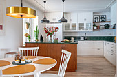An open-plan kitchen with a green marble worktop, a kitchen island and a dining area