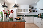 Open kitchen with green marble worktop, kitchen island and dining area
