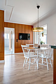 A dining area with a round, white table and chairs and a brass lamp pendant lamp