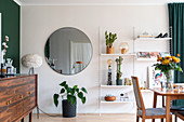 Sideboard in front of a green wall, round mirror and open shelf in the dining room