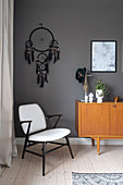 An armchair, a dream catcher and a sideboard in front of a dark wall in a bedroom