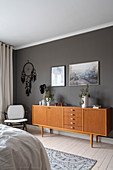 Armchair, dream catcher and sideboard in front of a dark wall in the bedroom
