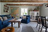 Polstergarnitur mit blauen Hussen, Couchtisch und Vitrinenschrank in ländlichem Wohnzimmer