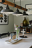 A vintage metal and wood pendant lamp above a dining table