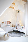 Fairy lights and paper lamps in teenager's attic bedroom decorated in white