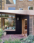 Modern extension with open façade structure made from wooden slats on brick house