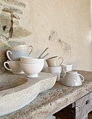 Cups in natural shades on rustic sink next to stone wall