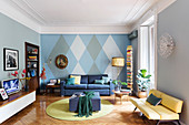 Seating furniture in a living room with a diamond-shaped wall pattern, stucco moulding and a parquet floor