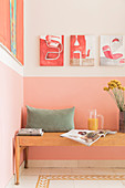 A wooden bench with pillows against a pink wall in a kitchen