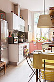 A fridge-freezer in a fitted kitchen with a table and garden chairs in the foreground