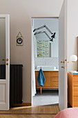 A view into a bathroom with a vanity unit and a wall lamp