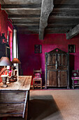 Antique wooden furniture and wood-beamed ceiling in room with purple wall