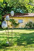 Stone sculpture in the garden, outbuilding in the background