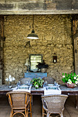 Long dining table with rattan chairs on the veranda of a stone house