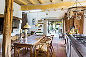 Wooden table with rattan chairs in country kitchen with wood-beamed ceiling