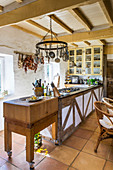 Long counter in a country kitchen with wooden ceiling beams