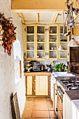 Long counter with gas cooker in country house kitchen with wooden beam ceiling