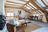 Sessel und Holztisch in ländlichem Dachzimmer mit Holzbalkendecke