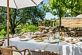 Set table under parasol on rustic terrace