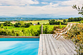 Deckchair at poolside with a view of the surrounding countryside
