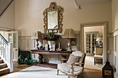 French style armchair and pair of french extra large green glass bottles in hallway with large console table