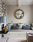 Gold-leaf convex mirror above blue and taupe daybed