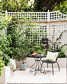 Chair and table in courtyard garden of Victorian terrace