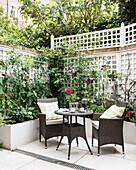 Wicker furniture in courtyard garden of Victorian terrace